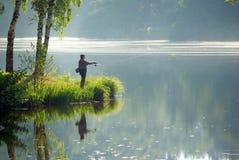 Pescador no lago Imagens de Stock