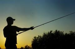Pescador no pôr-do-sol Imagem de Stock