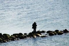 Pescador no sillhouette das pedras Imagem de Stock