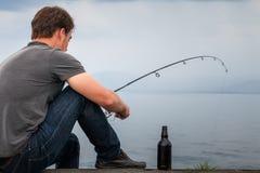 Pescador novo Fishing Mackerel sentado na doca imagens de stock