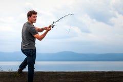 Pescador novo pronto para balançar a isca para travar a cavala fotografia de stock