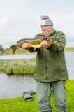 Pescador orgulloso con un lucio Imagenes de archivo