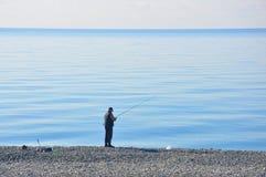 Pescador pelo mar imagem de stock