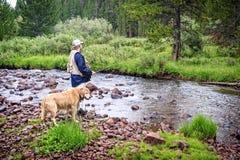 Pescador por una corriente con el perro Imagenes de archivo
