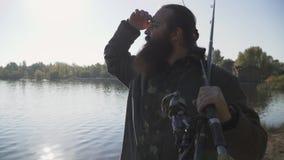 Pescador que anda com as duas hastes ao longo dos pares do banco de rio na distância à procura de um bom lugar para pescar filme