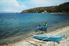 Pescador que arrastra su bote pequeño que se parqueará en la orilla de mar Fotos de archivo libres de regalías