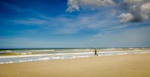 Pescador que camina en el mar Foto de archivo libre de regalías