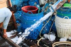 Pescador que espera descargando el hielo para los pescados congelados en el fishi fotos de archivo
