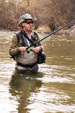 Pescador que está no rio ao pescar para o timalo fotografia de stock