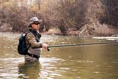 Pescador que está no rio ao pescar para o timalo imagem de stock royalty free