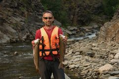 Pescador que guarda duas grandes trutas asiáticas Imagens de Stock