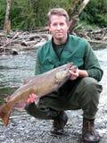 Pescador que guarda grandes peixes salmon com rio e madeiras dentro para trás foto de stock
