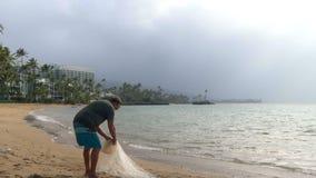 Pescador que guarda a rede de pesca na praia 4k vídeos de arquivo