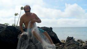 Pescador que guarda a rede de pesca na praia 4k filme