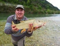 Pescador que guarda um peixe travado fresco imagens de stock royalty free