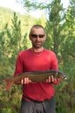 Pescador que guarda uma truta grande Foto de Stock Royalty Free