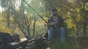 Pescador que hace girar pescando el carrete, sentándose en las piedras, disfrutando de ocio, otoño almacen de video