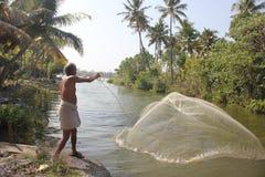 Pescador que joga para fora sua rede Imagens de Stock