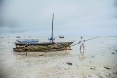 Pescador que limpa seu barco zanzibar tanzânia imagens de stock royalty free