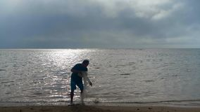 Pescador que lleva a cabo la red de pesca en la playa 4k almacen de video