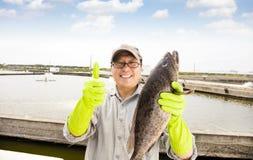 pescador que muestra pescados antes del estanque de peces de la cría imagen de archivo