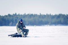 Pescador que pesca la pesca del invierno en un d?a soleado brillante imagen de archivo libre de regalías