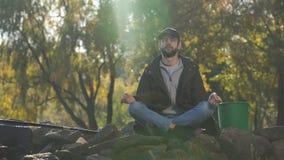 Pescador que reflexiona sobre la orilla del río, actitud del loto, asana de la yoga, relajación en salvaje almacen de metraje de vídeo