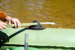 Pescador que rema el barco de pesca de goma inflable en la superficie del agua Mano del hombre que rema la paleta foto de archivo libre de regalías