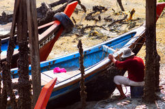 Pescador que repara o barco de pesca Fotos de Stock Royalty Free