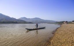 Pescador que se coloca en el barco de madera que trabaja en su red de pesca en el río de Mae Khong en Tailandia septentrional Fotos de archivo libres de regalías