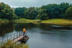 Pescador que se coloca en el embarcadero del lago y que pesca en día lluvioso foto de archivo
