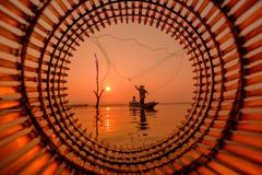 Pescador que se coloca en un barco de pesca para un pescado en el agua Fotos de archivo libres de regalías