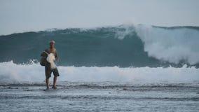 Pescador que se coloca entre olas oceánicas grandes Escena auténtica del hombre asiático que mira en la distancia y que pesca con almacen de metraje de vídeo