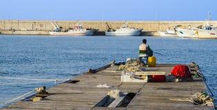 Pescador que se sienta en el muelle de un italiano del puerto Foto de archivo