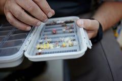 Pescador que seleciona uma mosca amarrada mão da pesca fotos de stock royalty free