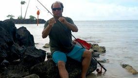 Pescador que sostiene los aparejos de pesca en la playa 4k almacen de metraje de vídeo