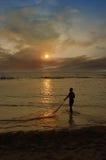 Pescador que usa la red para coger pescados durante puesta del sol Imagen de archivo