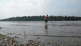 Pescador semidesnudo con una pesca de la caña de pescar en el río tranquilo almacen de metraje de vídeo