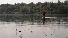 Pescador semidesnudo con una pesca de la caña de pescar en el río tranquilo metrajes