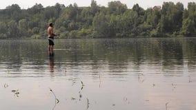 Pescador semidesnudo con una pesca de la caña de pescar en el río tranquilo almacen de video