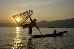 Pescador Silhouette no por do sol Fotografia de Stock