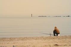 Pescador solitário na praia Fotografia de Stock Royalty Free