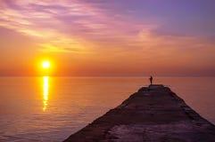 Pescador solitario en el embarcadero en la playa en la salida del sol Imagen de archivo libre de regalías