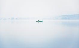 Pescador solo en el barco en una niebla gruesa en el lago en una mañana del otoño Foto de archivo libre de regalías