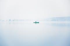 Pescador solo en el barco en una niebla gruesa en el lago en una mañana del otoño Fotos de archivo libres de regalías