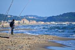 Pescador With Spinning na praia no mar Mediterrâneo, Itália Imagens de Stock