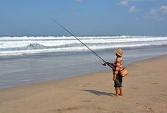 Pescador Surf Casting do Balinese na praia de Legian imagens de stock royalty free