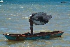 Pescador Throws una red de pesca por un barco de pesca Fotografía de archivo libre de regalías