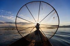 Pescador tradicional do birmanês no lago Inle, Myanmar famoso para seu um estilo de enfileiramento equipado com pernas distintivo imagem de stock