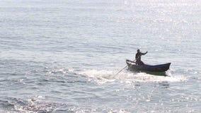 Pescador vietnamita Beats Water con el palillo en bote pequeño almacen de video